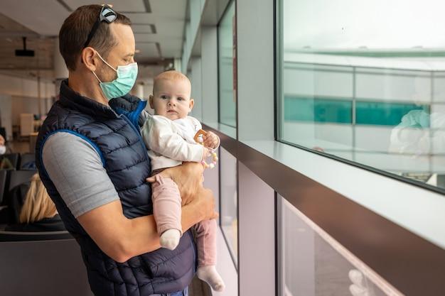 Отец в медицинской маске и его дочь ждут посадки на самолет в аэропорту Premium Фотографии