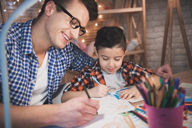 父親は息子が家で夜に紙に色鉛筆とマーカーで描くのを手伝っています。 Premium写真
