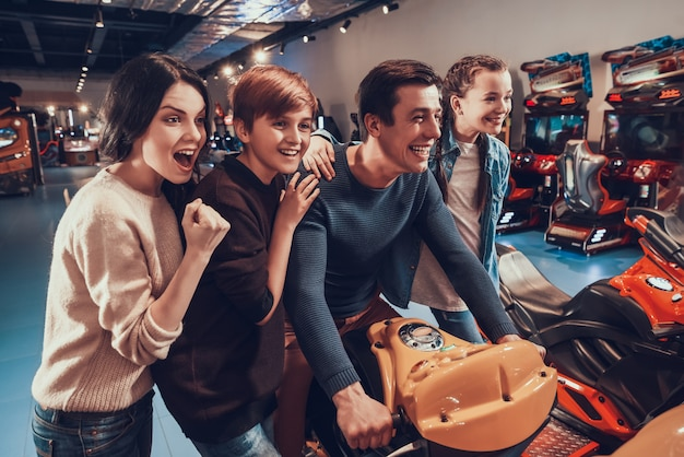 Father is riding orange motorcycle in arcade. Premium Photo