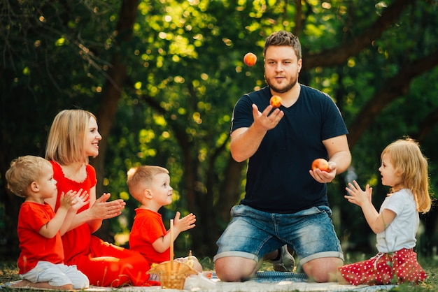 Father juggling oranges in front of his family Free Photo
