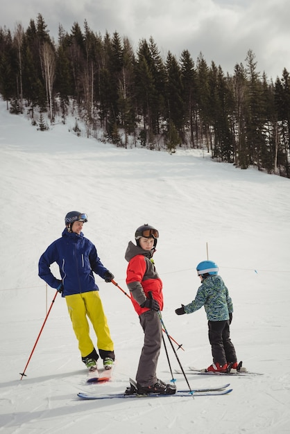Father and kids skiing on snowy alps Free Photo