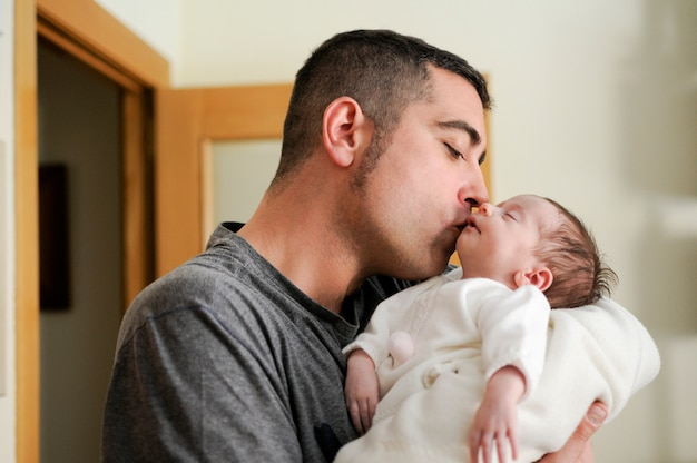 Father kissing his newborn baby girl. Free Photo