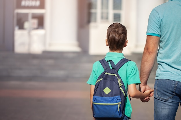 Father leads a little child school boy go hand in hand. parent and son with backpack behind the back. Premium Photo
