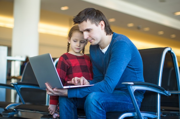 Father and little girl with laptop at the airport while waiting his flight Premium Photo