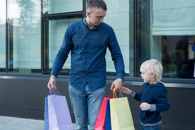 Father and little son with colorful shopping bags on the street. Premium Photo