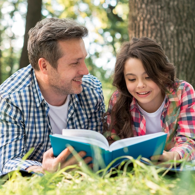 Father looking at his daughter while reading book in park Free Photo