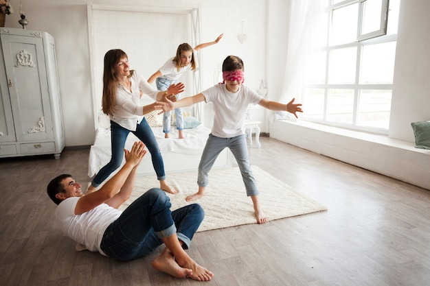 Father lying on floor while family playing blind man's buff at home Free Photo