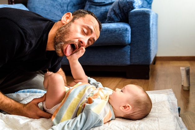 Father making funny gestures to his baby daughter while changing his diaper. Premium Photo