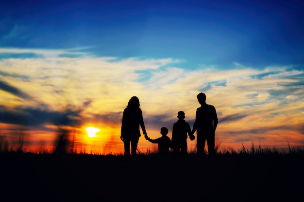 Father, mother, and children hold hands on a sunset background. Premium Photo