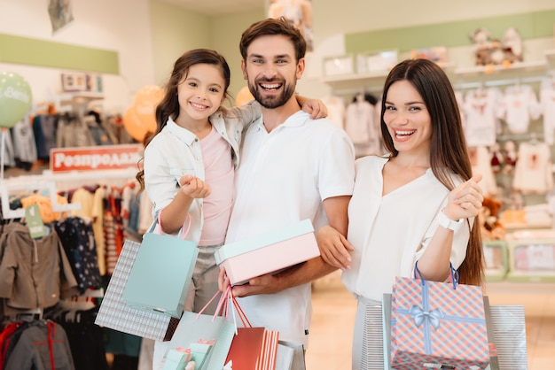 Father, mother and daughter are in clothes store Premium Photo