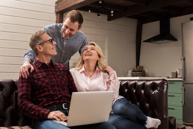 Father and mother on sofa with laptop and son Free Photo