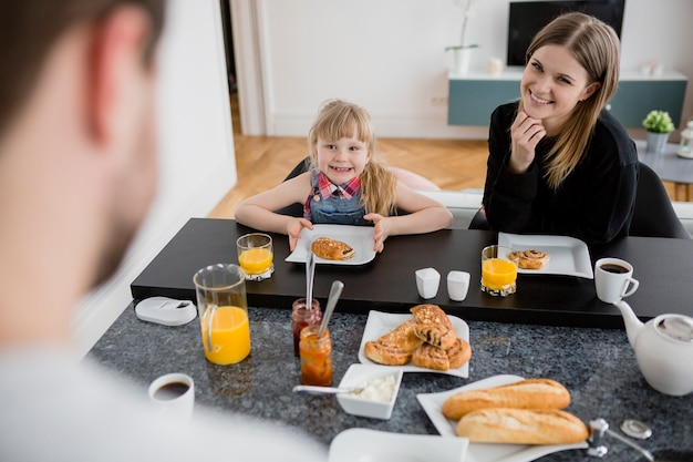 Father near mother and daughter having breakfast Free Photo