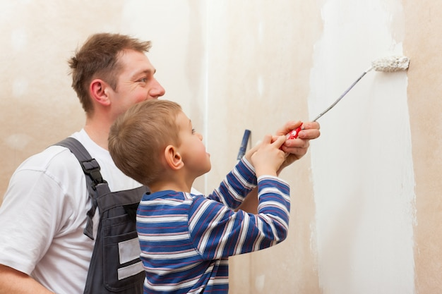 Father painting wall with child Premium Photo