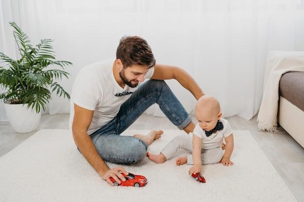 家で赤ちゃんと遊ぶ父 Premium写真