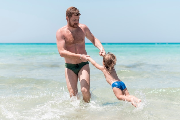 Father playing with child in the sea Free Photo