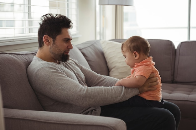 Padre che gioca con il suo bambino sul divano nel soggiorno Foto Gratuite