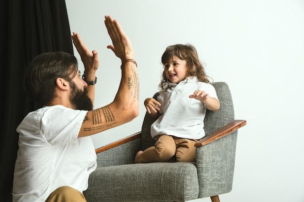 自宅の居間で幼い息子と遊んでいる父。休日や週末に子供たちと楽しんでいる若いお父さん。親子関係、子供時代、父の日、家族関係の概念。 無料写真