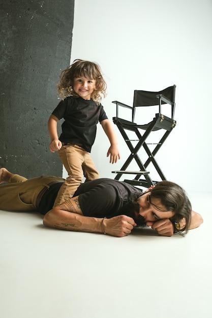 Padre che gioca con il giovane figlio nel salotto di casa. giovane papà che si diverte con i suoi figli in vacanza o nel fine settimana Foto Gratuite