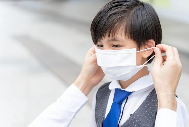 Отец надевает защитную маску на своего сына, азиатская семья носит маску для защиты Бесплатные Фотографии