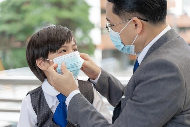 Padre che mette una maschera protettiva su suo figlio, famiglia asiatica che indossa una maschera per la protezione durante l'epidemia di coronavirus covid 19 in quarantena Foto Gratuite