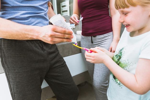 父親が娘の筆に練り歯磨きを塗る 無料写真