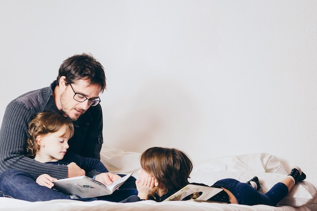 Father reading book to daughters in bed Free Photo