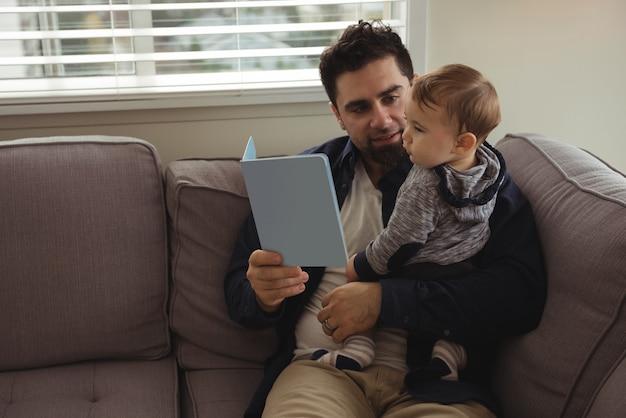 Padre che legge un libro mentre si tiene il suo bambino Foto Gratuite