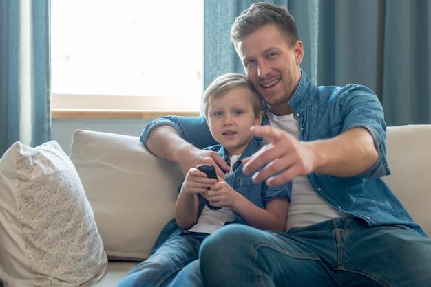 День отца папа и сын смотрят телевизор Premium Фотографии