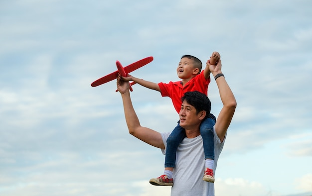 Father's day. dad and baby son playing together outdoors paper plane Premium Photo