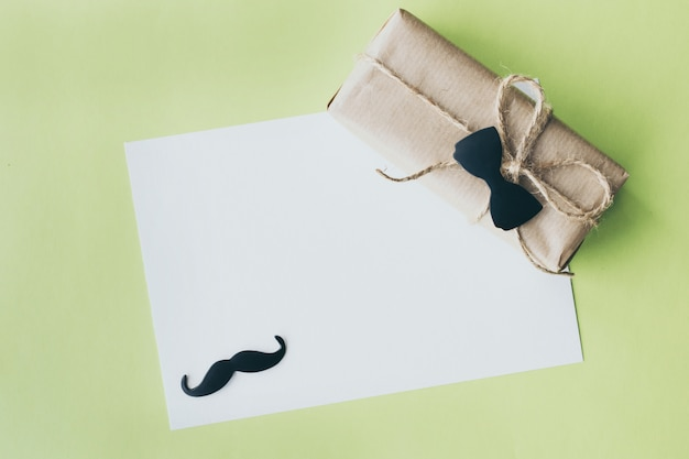 Father's day. gift package wrapped with paper and rope with a decorative bow-tie on green background. copyspace Premium Photo