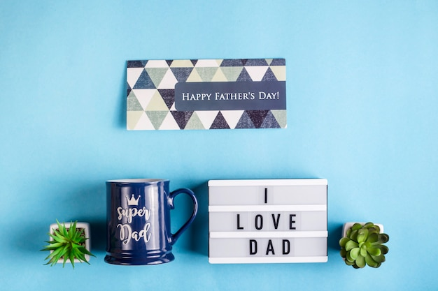 Father's day layout with a gift cup, a card and the inscription i love dad Premium Photo