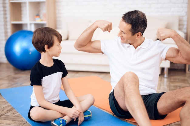 The father shows his son his muscles. Premium Photo