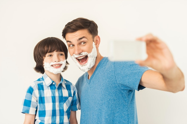 The father shows his son how to shave in the bathroom Premium Photo