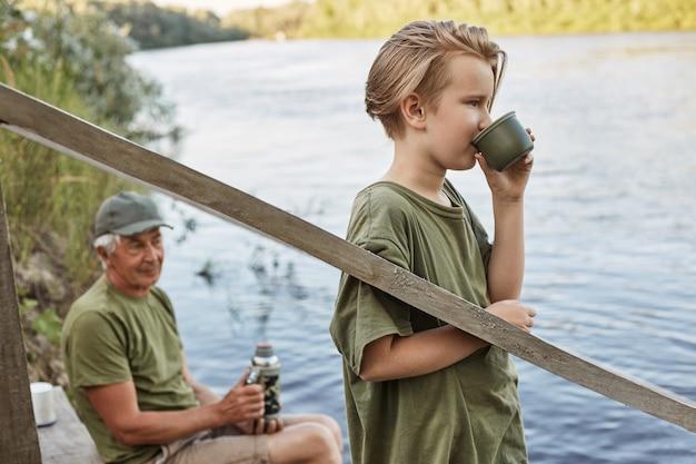 Будьте отцом сидеть на деревянном размещении водя с термосом в руках и смотря в расстоянии к реке, его сын выпивая горячий чай и наслаждаясь красивой природой. Premium Фотографии