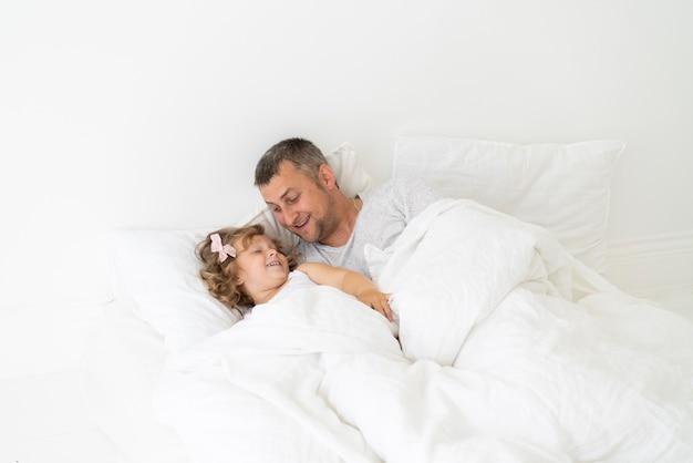 寝室で娘と一緒に座っている父 無料写真