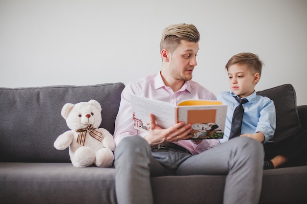 Father sitting with his son on the sofa and reading a story Free Photo