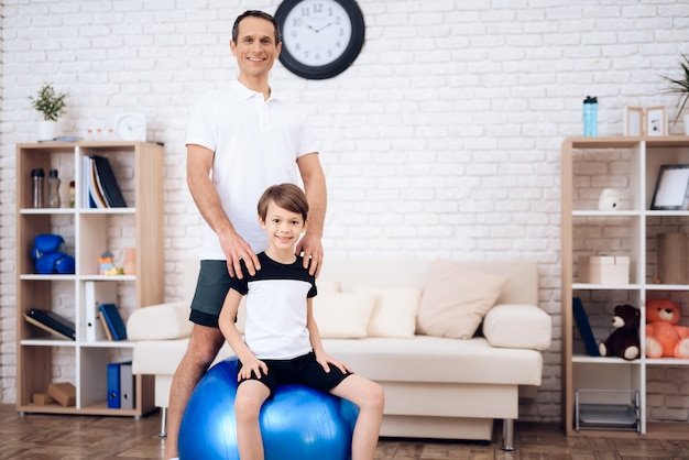 Father and son are engaged in fitness together with fitball. Premium Photo