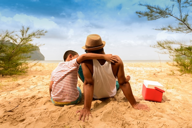 Father and son are happy for picnic with sea view. Premium Photo