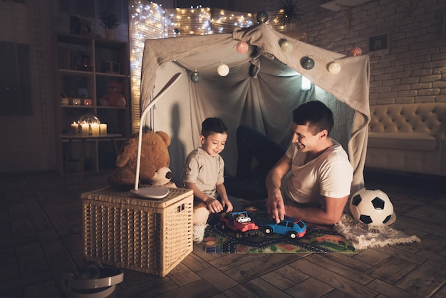 Father and son are playing with toy cars at night at home. Premium Photo
