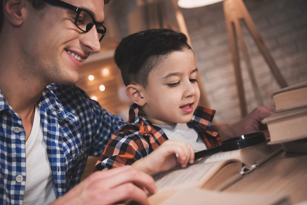 Father and son are reading fairy tales book at night at home Premium Photo