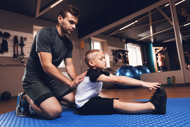 Father and son are stretching each other in gym. Premium Photo