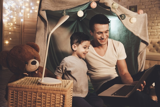 Father and son are watching movie on laptop at night at home Premium Photo