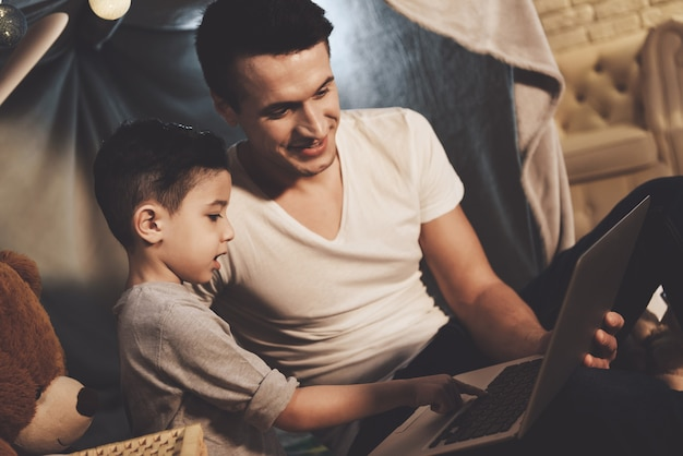 Father and son are watching video on laptop at night at home Premium Photo
