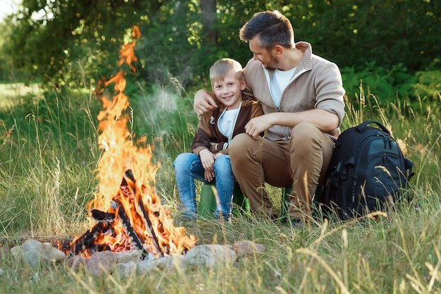 Father and son by the fire on green nature. Premium Photo