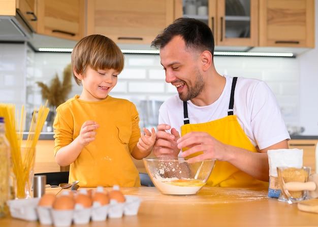 Father and son cracking eggs for cooking Free Photo