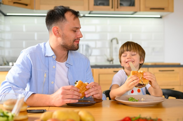 Father and son eating delicious burgers Free Photo