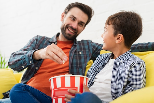 Father and son eating popcorn and looking at each other Free Photo