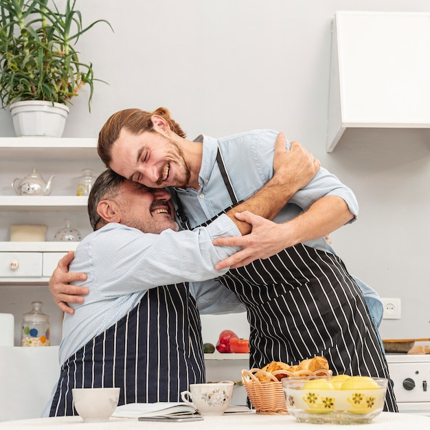 Father and son embracing in kitchen Free Photo