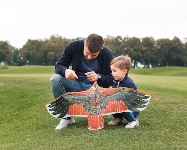 Father and son fixing a kite Free Photo
