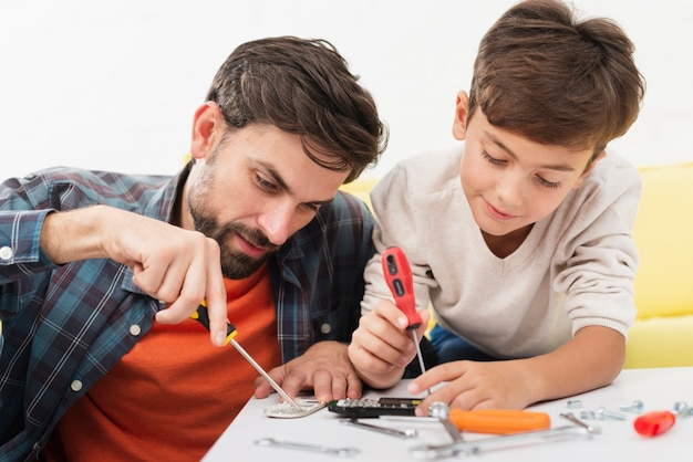 Father and son fixing toy cars Free Photo